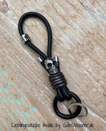 Schlüsselband mit Skull und Karabiner-Ring. 14 cm Nappaleder in Schwarz. Bestückt mit einem Ring-Karabiner in Schwarz. Dekoriert mit hochwertigem Totenkopf, Schlüsselring, Logo-Perle und Edelstahl-Endkappen. Gesamtlänge 16 cm.
